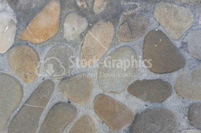 Round rocks on cement wall