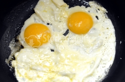 Close-up photo of two scrambled eggs in black frying pan