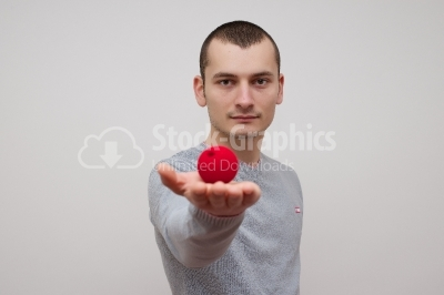 Man holding a red ball looking to the camera