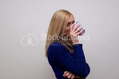 Blond girl drinking coffee or tea and smiling