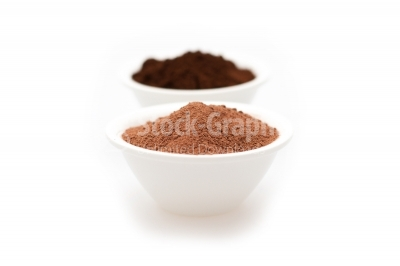 Cocoa powder and ground coffe in two white bowls