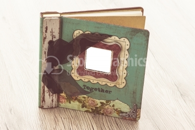 A aged photo album sits on a rustic wooden background