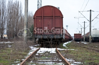 Back of a steam train with a rail car at the end on a track