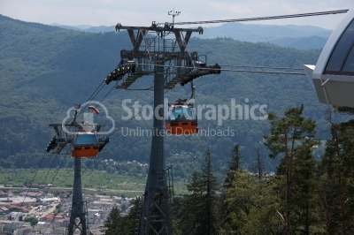 Urban cable car running across the forest and city