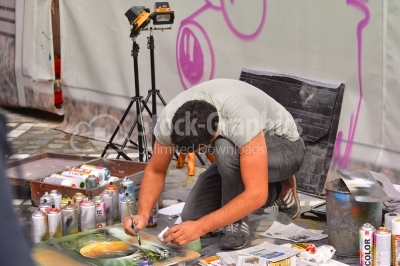 Young artist working on the street creating spray paint art.