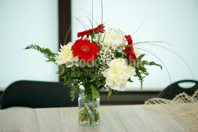 Beautiful bright gerbera in glass vase on wooden background