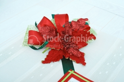 Red artificial flower on top of a hand made gift box