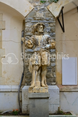 Statue in front of beautiful Peles castle and ornamental garden