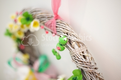 Funny frog sitting on a spring wreath