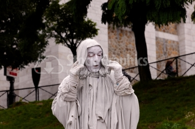 Street artist playing disguised as a white statue