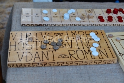 A Roman bone dice and gaming counter on a wooden table