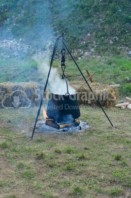 Food in a cauldron on a fire. Cooking outdoors in cast-iron caul