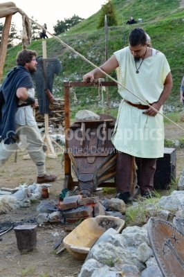 Blacksmith working on a medieval festival with old tools