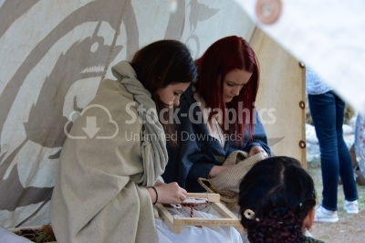 Young girls using old looms on an ancient festival