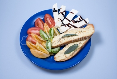 Fresh tomatoes, chees and bread on a blue plate