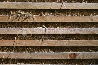 Fence planks on a background of dry straw