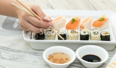 Woman hand arranging sushi rolls
