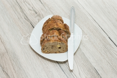 Bread cut sliced ​​on a white plat, with knife