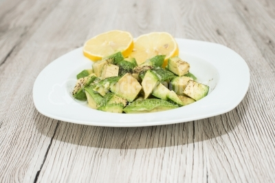 Avocado salad with lemon on wooden surface
