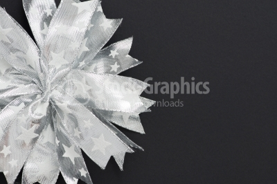 Christmas background. Silver bow decorations on a dark backgroun
