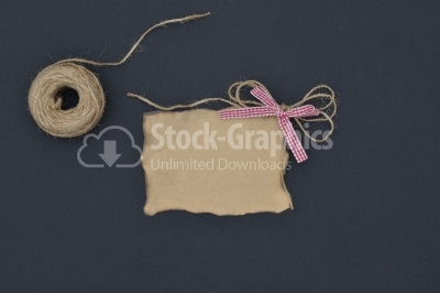 Close up of a note card with ribbon bow on black background