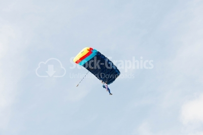 Low-angle skydiver flying on colorful parachute