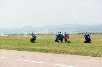 Skydivers with parachutes land on ground