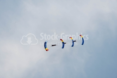 Airfield festival with flying skydivers on the blue sky