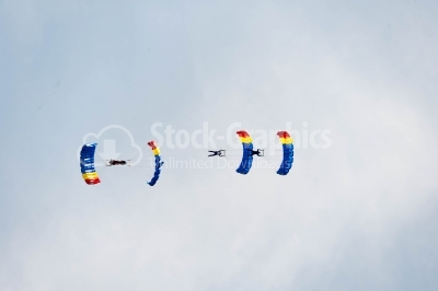 Cloudy sky crossed by skydivers