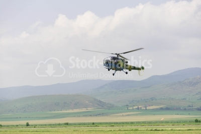 Flying army helicopter over the plain