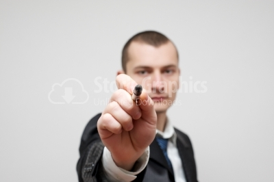 Young businessman pointing with the pen at you.