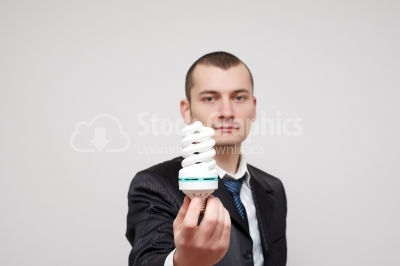 Young businessman holding a light bulb