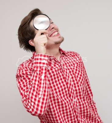 Businessman looking through magnifying glass.