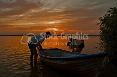 2 men at sunset with boat