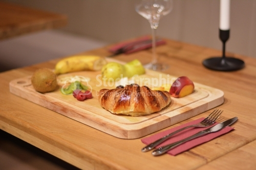 A croissant and fruit on a wooden platter.