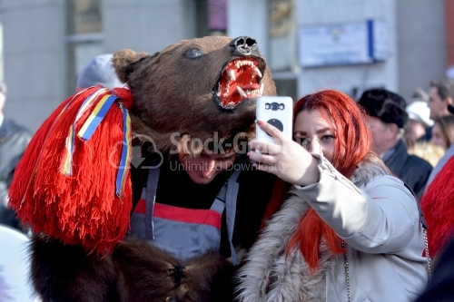 A man dressed as a bear and a young woman takes her own photo.