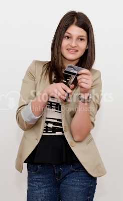 A young woman is cutting through her credit card with scissors.