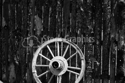 An old rusty wagon wheel leaning on a barn wall in black and whi