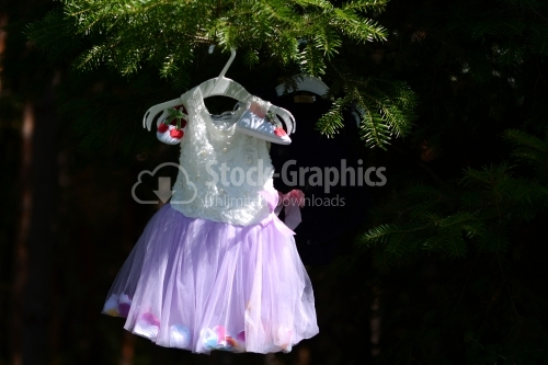 Baby girl costume hanged on a tree