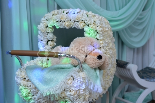 Baby stroller with flowers and teddy bear