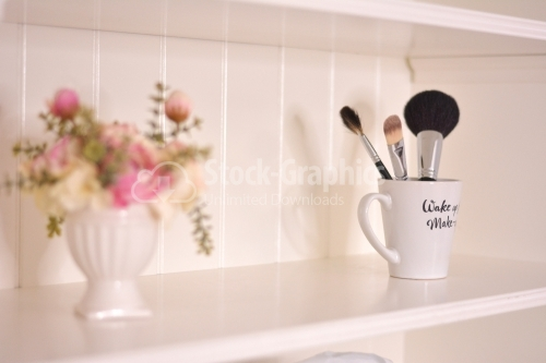 Bathroom shelf with flowers and brushes