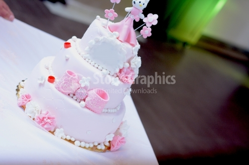 Beautiful pink birthday cake with little figurine on top