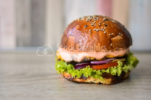 Beef burger seen from the front, on the wooden table