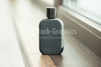 Black perfume bottle sitting on the window