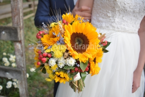 Bride and groom and a bouquet of flowers in hand, the bouquet has summer flowers especially sunflower.