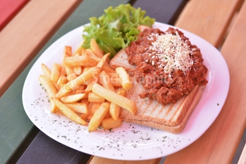 Bruschetta with minced meat and cheese, french fries and lettuce.