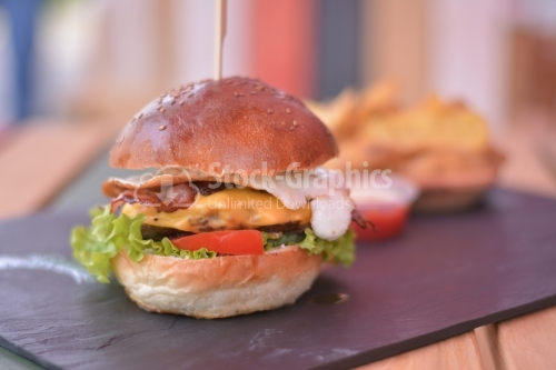 Burger menu with egg, chicken, beef, tomatoes and salad, on the black slate signboard