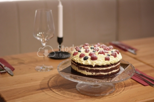 Cake with cocoa top, vanilla cream and berries.