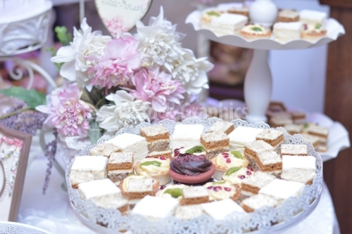 Cakes with white cream and pink flowers on background