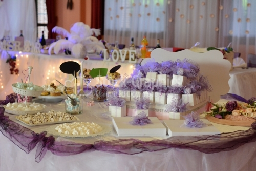 Candy bar on wedding party with a lot of different candies, cupcakes, souffle and cakes. Decorated in purple and white colors, indoor.